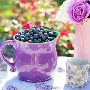Blueberries in pitcher on table next to coffee coup and flowers